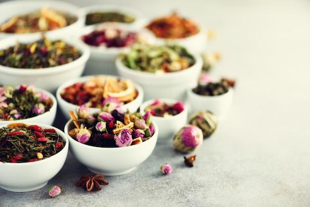 Assortiment van droge thee in kommen. thee soorten: groen, bloemen, kruiden, munt, melissa, gember, appel, roos, lindeboom, fruit, sinaasappel, hibiscus, framboos, korenbloem, cranberry Premium Foto