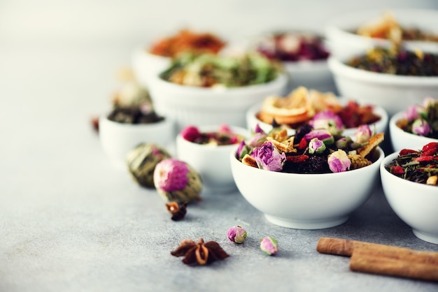 Assortiment van droge thee in witte kommen. Premium Foto