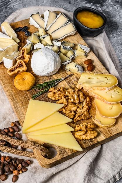 Assortiment van franse kaas met honing, noten en vijgen op snijplank. grijze achtergrond. bovenaanzicht Premium Foto