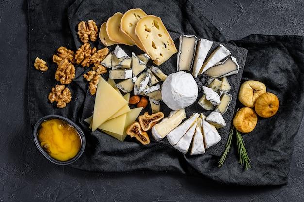 Assortiment van franse kaas met honing, noten en vijgen op snijplank. italiaanse antipasto. zwarte achtergrond. bovenaanzicht Premium Foto