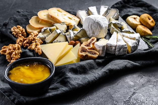 Assortiment van franse kaas met honing, noten en vijgen op snijplank. zwarte achtergrond. bovenaanzicht Premium Foto