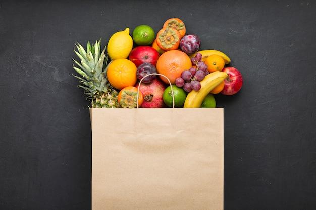 Assortiment van fruit in een papieren zak op zwart beton. concept van vitamines in de menselijke voeding. Premium Foto