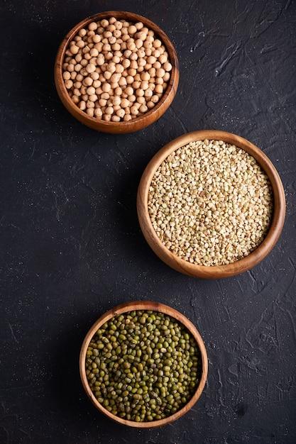 Assortiment van granen, peulvruchten, granen, granen, linzen, kikkererwten, erwten, bonen in houten kommen Premium Foto