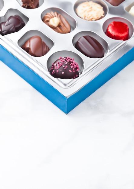 Assortiment van het suikergoedverscheidenheid van de luxe witte en donkere chocolade in zilveren plastickdienblad op marmeren achtergrond Premium Foto