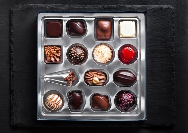 Assortiment van het suikergoedverscheidenheid van de luxe witte en donkere chocolade in zilveren plastickdienblad op zwarte steenachtergrond Premium Foto