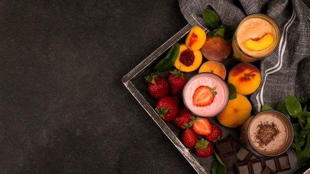 Assortiment van milkshakeglazen op dienblad met fruit en chocolade Gratis Foto