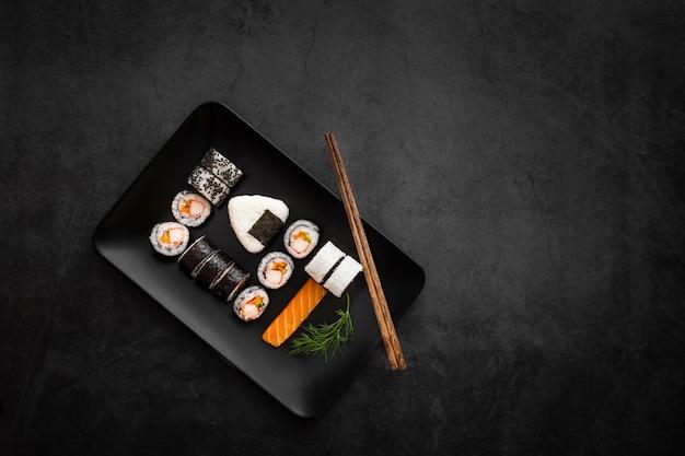 Assortiment van sushi op zwarte rechthoekige plaat met kopie ruimte Gratis Foto