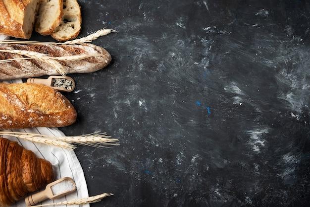 Assortiment van vers brood, bakken ingrediënten. stilleven van bovenaf vastgelegd. gezond zelfgebakken brood. achtergrond met copyspace. Premium Foto