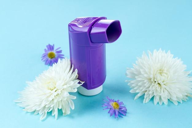 Astma-inhalers en bloemen op blauw Premium Foto
