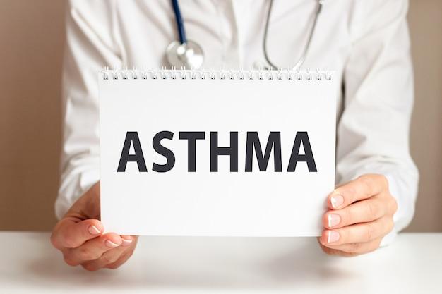 Astma-kaart in handen van arts. doctor's handen een vel papier met tekst astma, medische concept. Premium Foto