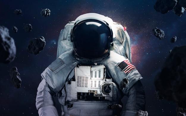 Astronaut ruimtewandeling bij de ontzagwekkende kosmische achtergronden met gloeiende sterren en asteroïden Premium Foto