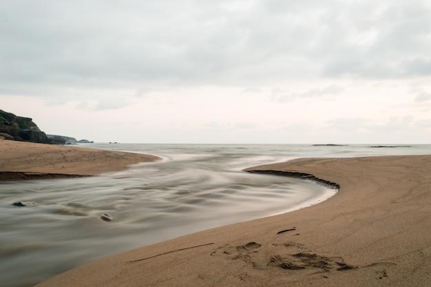 Atlantische oceaan. op de voorgrond stroomt een beek de zee in Premium Foto