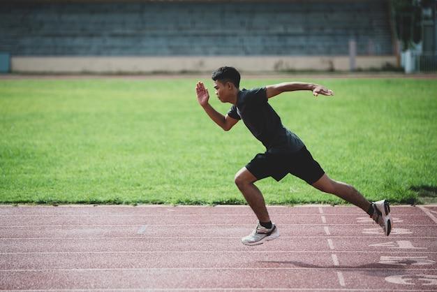 Atleet die zich op een renbaan voor alle weersomstandigheden bevindt Gratis Foto