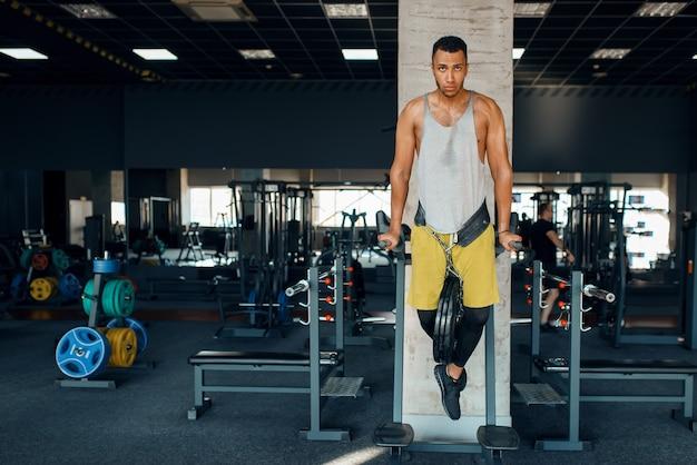 Atleet doet push-ups op de ongelijke balken in de sportschool Premium Foto