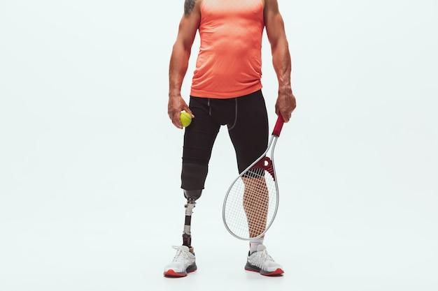 Atleet met een handicap of geamputeerde die op wit wordt geïsoleerd. professionele tennisser met beenprothese training Gratis Foto