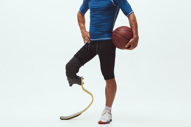 Atleet met een handicap of geamputeerde die op witte studioruimte wordt geïsoleerd. professionele mannelijke basketbalspeler met beenprothese die en in studio opleiden oefenen. Gratis Foto