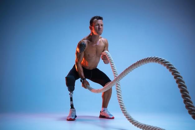 Atleet met een handicap of geamputeerde geïsoleerd op blauwe studio achtergrond. professionele mannelijke sportman met beenprothese training met gewichten in neon. Gratis Foto