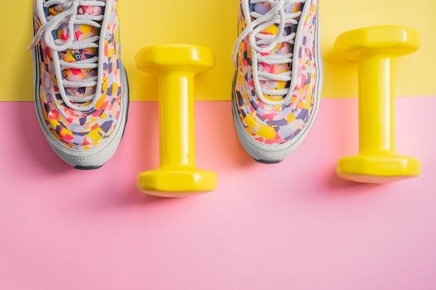 Atleet set met vrouwelijke lopende sneakers en halters geel-roze achtergrond. fitness concept. apparatuur voor gym en thuis Premium Foto