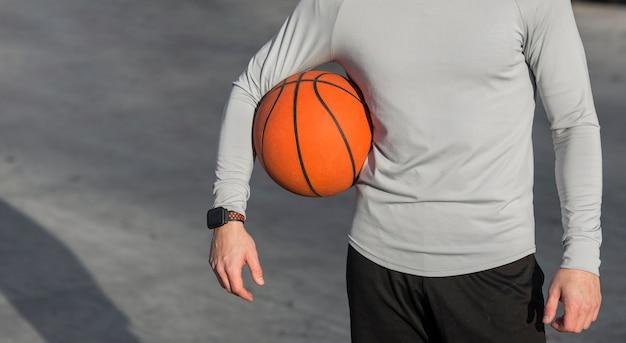 Atletisch mannelijk lichaam en een basketbal Gratis Foto