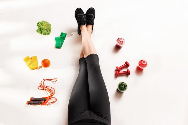 Atletisch meisje met gezond voedsel op de vloer Gratis Foto
