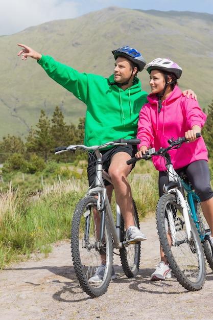Atletisch paar op een fietsrit die verbindingsdraden met een kap met mens het richten dragen Premium Foto