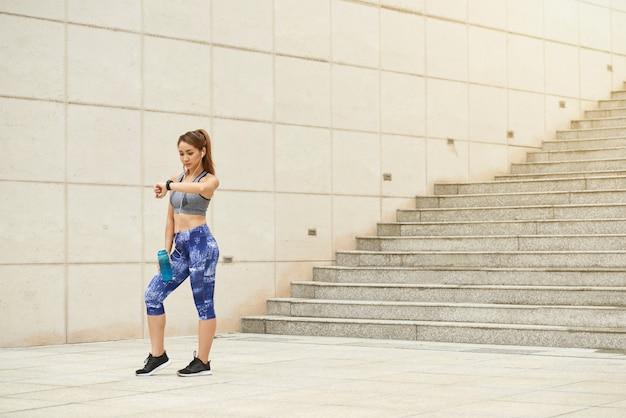 Atletische aziatische vrouw die zich in openlucht met waterfles bevindt en polshorloge bekijkt Gratis Foto