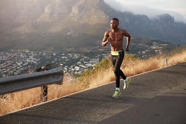 Atletische gezonde man loopt langs de weg buitenshuis, bestrijkt lange afstanden, bereidt zich voor op de marathon. sportieve mannelijke oefeningen bergafwaarts, dragen sportschoenen, leggings, in goede conditie zijn Gratis Foto