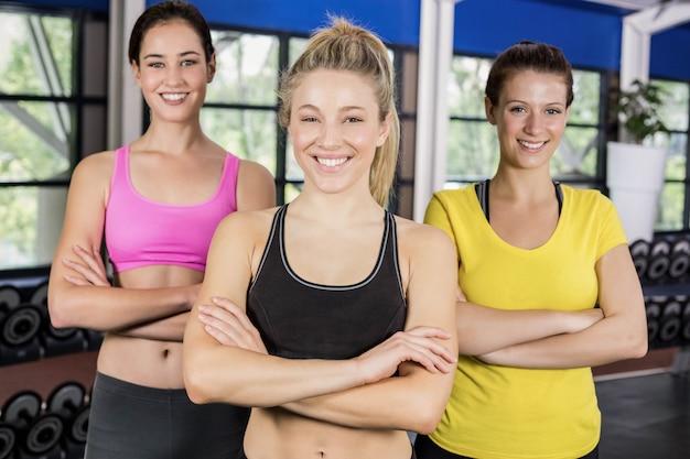 Atletische glimlachende vrouwen die met wapens stellen die in crossfitgymnastiek worden gekruist Premium Foto