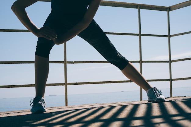 Atletische jonge vrouw die ochtendoefeningen op de achtergrond van het overzees doet Premium Foto