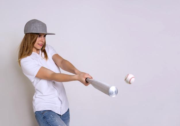 Atletische jonge vrouw met een honkbalknuppel raakt de bal Premium Foto