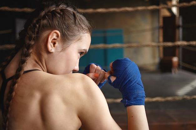 Atletische jonge vrouw met twee vlechten en gespierde rug die handwraps draagt die zich in defensieve houding bevinden Gratis Foto