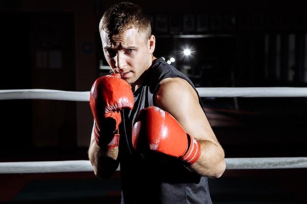 Atletische jongeman in bokshandschoenen boksen in de ring. Premium Foto