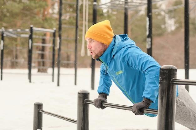 Atletische jongeman in gele hoed en handschoenen doet push-ups van bar op winter training grond Premium Foto