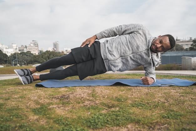 Atletische man doen oefening in het park Premium Foto