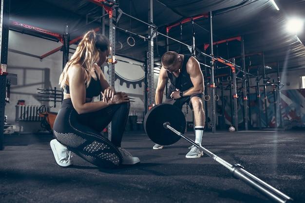 Atletische man en vrouw met halters Gratis Foto