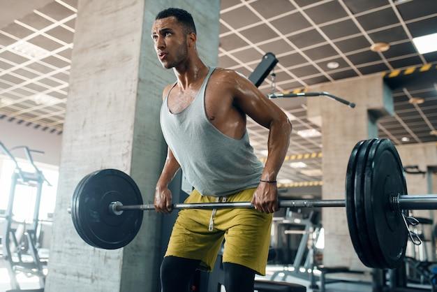Atletische man in sportkleding oefening met barbell op training in de sportschool doet. Premium Foto