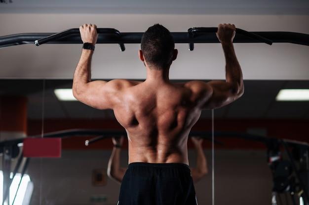Atletische man maken pull-up oefeningen op een lat in de sportschool Premium Foto