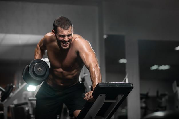 Atletische man traint met halters, pompen zijn biceps Premium Foto