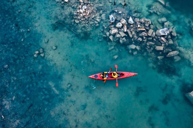 Atletische man twee drijft op een rode boot in de rivier Gratis Foto