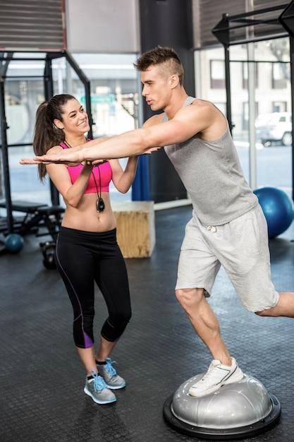 Atletische man uitwerken geholpen door trainer vrouw bij gymnastiek Premium Foto