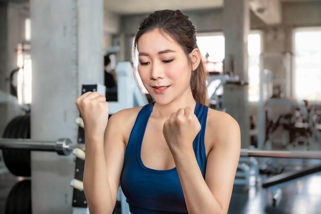 Atletische mooie vrouw fit en gezond lachend in de sportschool na training. Premium Foto
