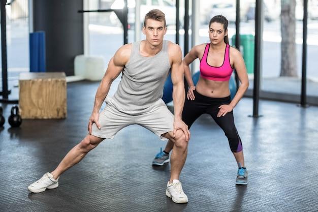 Atletische paar die zich uitstrekt in de sportschool Premium Foto