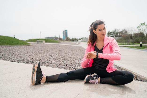 Atletische vrouw benen strekken voor oefening Gratis Foto