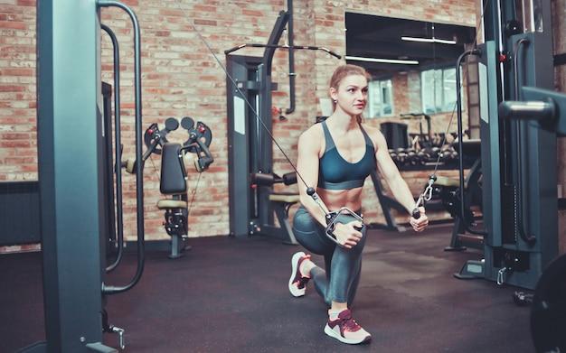 Atletische vrouw in sportkleding die oefening in een crossovermachine doen in de gymnastiek. Premium Foto
