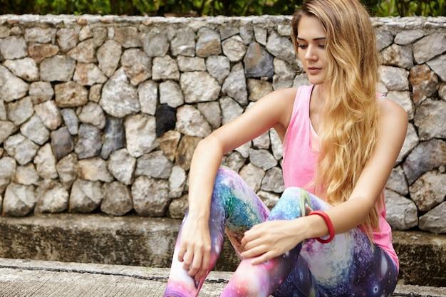 Atletische vrouw met lang blond haar herstellen van training, zittend op de stoep in stadspark. Gratis Foto