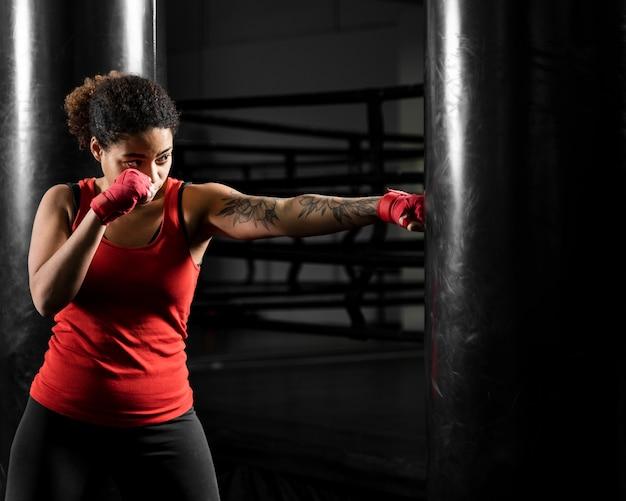 Atletische vrouw training in bokscentrum Gratis Foto