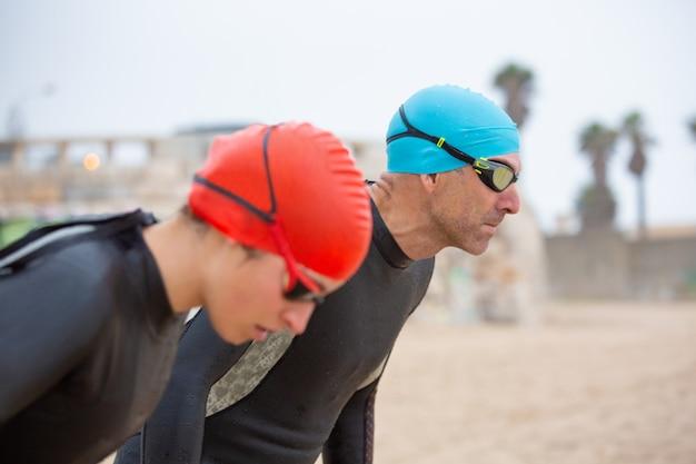 Atletische zwemmers in wetsuits op het strand Gratis Foto