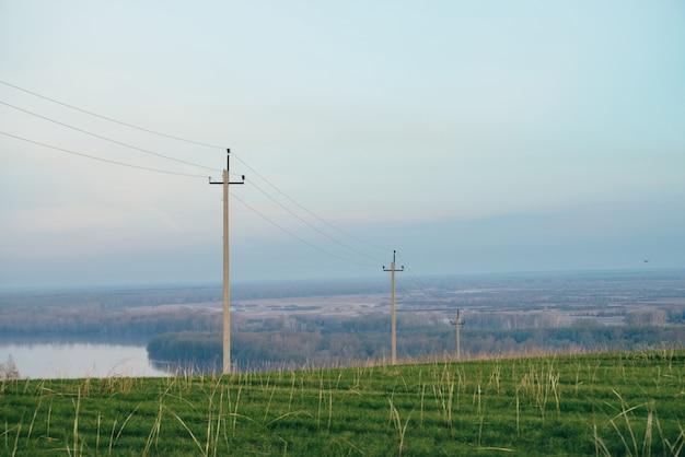 Atmosferisch landschap met hoogspanningslijnen in groen veld op de achtergrond van de rivier onder de blauwe hemel Premium Foto