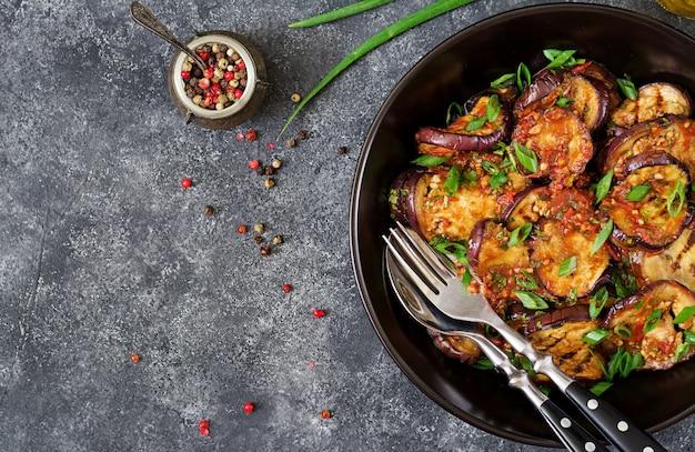 Aubergine gegrild met tomatensaus, knoflook, koriander en munt. veganistisch eten. gegrilde aubergine. bovenaanzicht plat leggen Gratis Foto