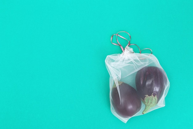Aubergines in herbruikbare eco-zakjes. verse groenten in zakken van transparant textiel voor opslag van voedsel. plastic vrij concept. plat liggen. bovenaanzicht. Premium Foto
